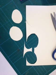 2. Out of a cream card cut ovals for the faces. The spaces between the ovals make perfect neck shapes.